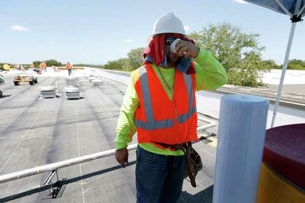 Jose Hernandez grabs a cup of water before returning to work as Beldon Roofing workers attend to a job at Sunshine Cottage during the heat of the day on Friday, July 21, 2017.