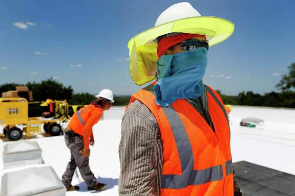 Isaac Cruz Saucedo protects himself from extreme sun exposure as Beldon Roofing workers take on a job at Sunshine Cottage during the heat of the day on Friday, July 21, 2017. When climate scientists look at how global warming will change San Antonio, one clear signal emerges: An already-hot city is going to get hotter. By 2040 to 2060, nearly every day of an average July or August will be above 100 degrees, according to one computer model. That kind of warming is going to drive northward shifts in plant and animal ranges, lower agricultural productivity and a decline in the outdoor labor force. Predicting rainfall in the future is more difficult. While climate models predict a slight increase in intense rainstorms with longer dry periods in between, climate scientists say that we are heading into the unknown.