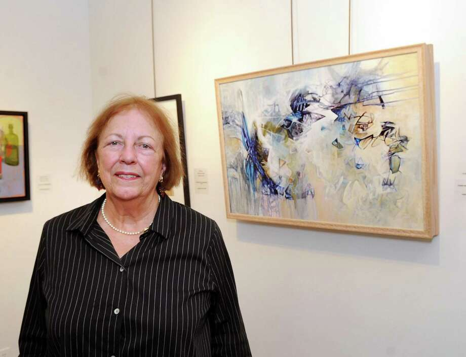 """Christine Irvin, president of the Stamford Art Association, stands by the work of first place winner Thyra Moore of Maryland, titled """"Inquisitive,"""" an acrylic on canvas, that is part of the 37th annual Faber Birren National Color Award Show at the Stamford Art Association Gallery in Stamford, Conn., Friday, Sept. 15, 2017. The opening for the show, that celebrates artists and their use of color in the tradition established by Birren, a noted Stamford color theorist who passed away in 1988, is Sunday, Sept. 24, from 4 p.m. - 6 p.m. at the gallery located at 39 Franklin Street. Photo: Bob Luckey Jr. / Hearst Connecticut Media / Greenwich Time"""