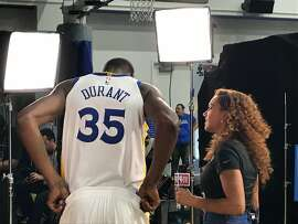 Kevin Durant does a TV spot at Warriors Media Day, Sept. 22, 2017, while other team members pose for photos