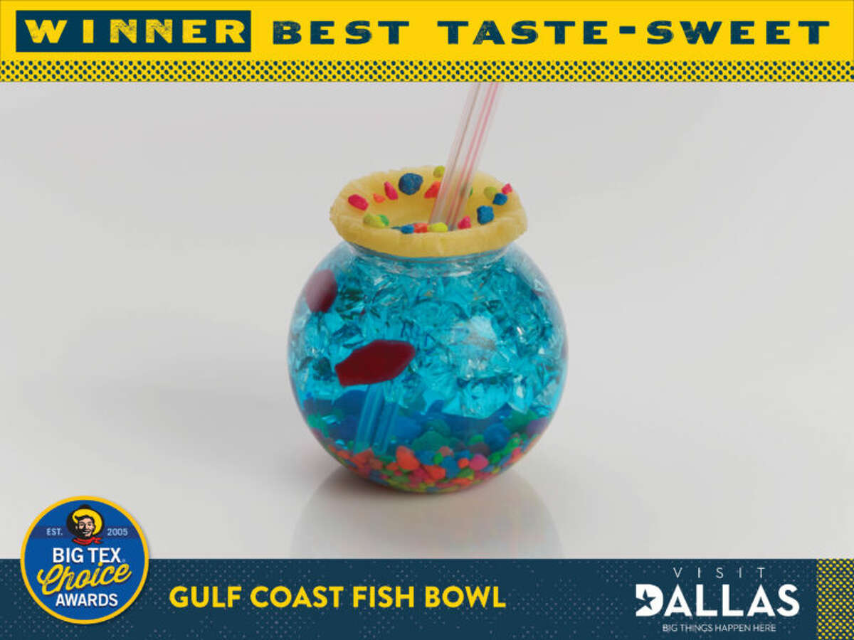 Gulf Coast Fish Bowl by Clint Probst *Big Tex Choice Award Winner - Best Taste: Sweet* A whimsical beverage featuring all the flavors of your favorite tropical coast, with a kick! Your drinkable aquarium begins with Nerds® candy gravel. Next, the drink is iced and filled with a specially-formulated blue alcoholic punch. Swedish Fish® swim through the ice while a pineapple slice serves as the lid! Each sip brings a stream of crunchy candy and tropical punch up the straw causing a flavor explosion that transports you beachside with every sip!