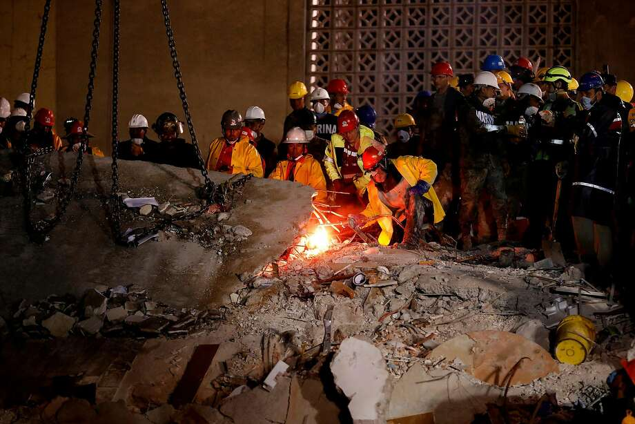Rescue teams use a blowtorch to cut rebar to free a slab of cement to be removed by crane while working at night looking for people trapped underneath the rubble of a collapsed six-story residential building in Colonia Condesa, in Mexico City, on Sept. 20, 2017. Photo: Gary Coronado, TNS