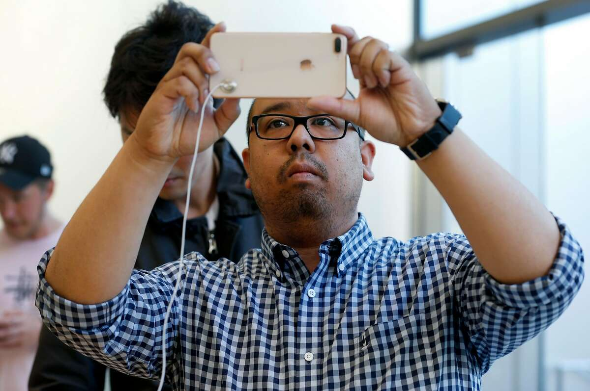 Charles Naval tests the camera on an iPhone 8 after it went on sale to the public at the Union Square Apple Store in San Francisco, Calif. on Friday, Sept. 22, 2017.