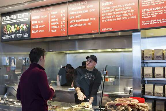 A Chipotle Mexican Grill employee prepares a burrito for a customer in Seattle in 2015. Amazon has teamed up with a company called Olo, which provides digital order and pay technology to 200 restaurant brands with about 40,000 U.S. locations, potentially giving Amazon access to a slew of delivery orders.