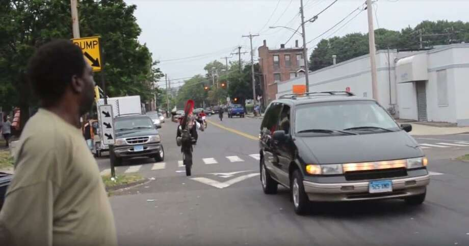 """A screenshot from a 2012 video titled """"New Haven Bike Life V2.0"""" featuring an unidentified man on a dirt bike riding alongside a car on road in New Haven. It's illegal for dirt bikes and ATV's to ride on public roads. Photo: Screenshot Via YouTube Channel Sp00nFedFilms"""