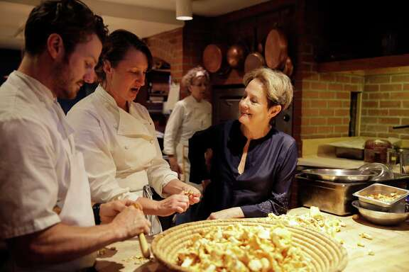 "In this photo taken Friday, Aug. 25, 2017, Alice Waters, right, talks with chefs Brian Bligh, left, and Beth Wells in the kitchen of the Chez Panisse restaurant in Berkeley, Calif. Waters' journey from a childhood of 1950s convenience cooking to the pinnacle of American cuisine is the subject of her new memoir, ""Coming to My Senses: The Making of a Counterculture Cook.""  (AP Photo/Eric Risberg)"