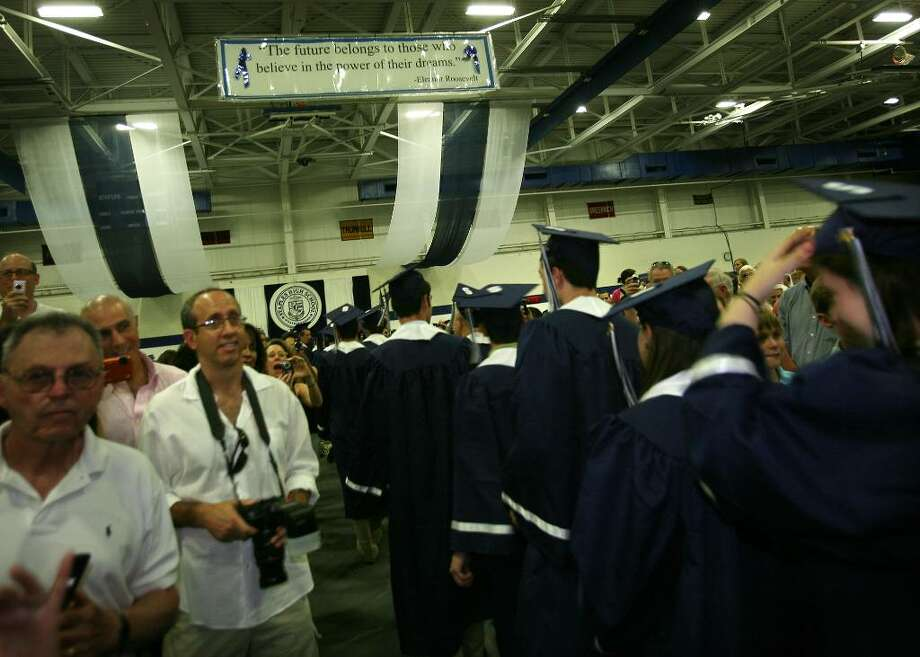 Graduates march in as family members jockey for photo position at the Staples High School graduation, Wednesday afternoon, June 23, 2010 in Westport. Photo: Brian A. Pounds / Connecticut Post