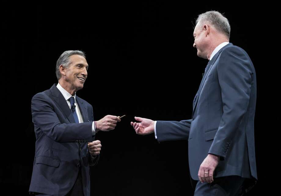 Howard Schultz (left) hands over the key to the original Starbucks store to President and Chief Operating Officer Kevin Johnson during last year's Starbucks annual meeting of shareholders on March 22, 2017 in Seattle. Photo: Stephen Brashear/Getty Images