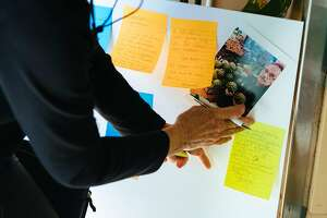 Sue Rugtiv places her note on a memorial board for Gus Vardakastanis at the Haight Street Market in San Francisco, Calif. Friday, September 22, 2017.