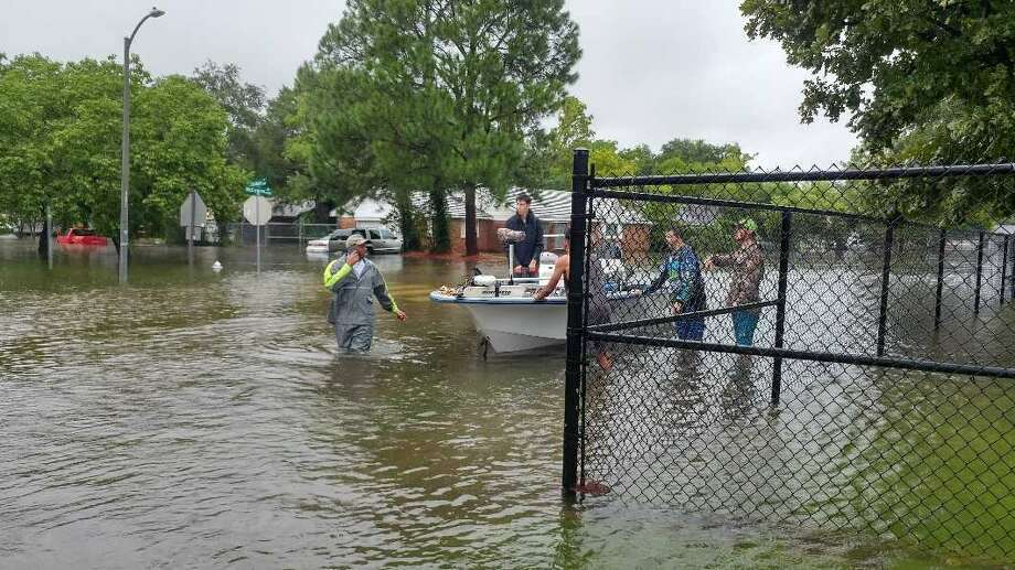 Neighborhood rescuers take flood victimsin Westbury neighborhood by boat to a makeshift shelter at Anderson Elementary. Patricia Noren and her family were among those who found haven there after their house flooded. Photo: Jorge Rodriguez Photo
