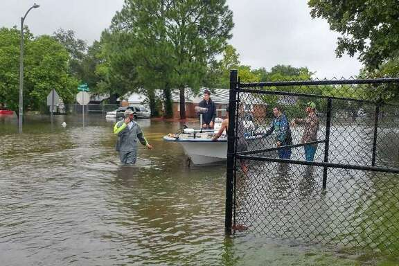 Neighborhood rescuers take flood victims in Westbury neighborhood by boat to a makeshift shelter at Anderson Elementary. Patricia Noren and her family were among those who found haven there after their house flooded.