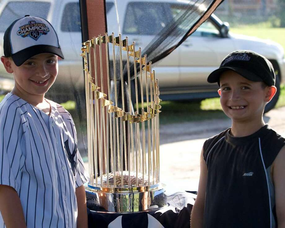 Yankee fans from New Milford, Brandon Rigdon, left, and Nicholas Bon Tempo admire the Yankees' 2009 World Series championship trophy which was on display Thursday night at Rogers Park. Photo: Barry Horn / The News-Times Freelance