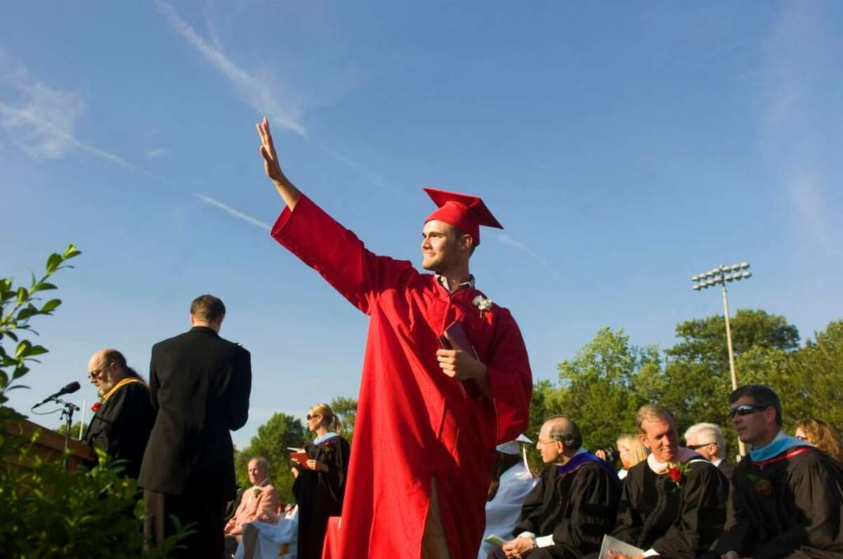 Ryan Frattaroli waves to his family after collecting his diploma at the New Canaan High School Class of 2010 graduation ceremony Wednesday, June 23, 2010.