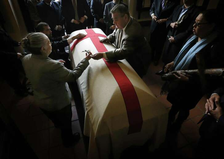 Esperanza Tijerina is handed a cross to place on the coffin of her husband, activist Reies López Tijerina, on Jan. 31, 2015, at Sacred Heart Church in El Paso. A land-grant activist, he became nationally known after a 1967 armed raid on the Rio Arriba County Courthouse in New Mexico.