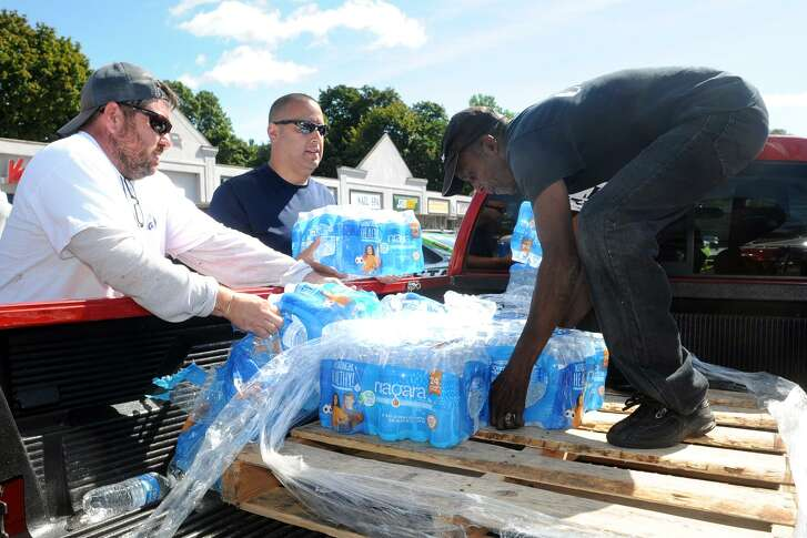 Volunteers unload a pickup truck full of bottled water during a Hurricane Harvey relief event held outside Vazzys Restaurant in Bridgeport, Conn. on Sept. 8. Critics of price gouging — the opposite of what is occurring here — are often portrayed as economically ill informed. Morality should temper markets in times of crisis.