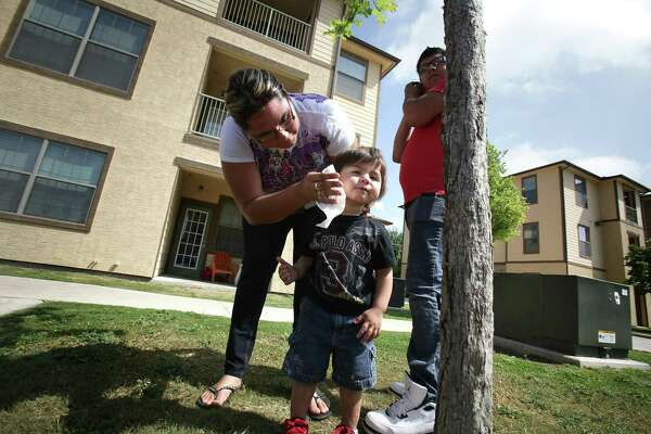 In 2012, Genia Machado cleans son Alius Machado's face. She and husband Elijah Machado lived at Mission Del Rio apartments on San Antonio's South Side, but Elijah had to drive to the other side of the city for his work. This is a symptom of San Antonio's entrenched poverty and the city's failure to treat it adequately.