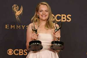 "Elisabeth Moss poses with the awards for Outstanding Drama Series and Outstanding Lead Actress in a Drama Series for ""The Handmaid's Tale"" during the 69th Emmy Awards at the Microsoft Theatre on September 17. The show's success can likely be linked to fevered imaginings that Trump's U.S. is on a similar path to theocratic dystopia."