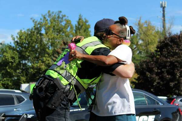 Zeronia Gordon, of Norwalk, hugs Wilton Police Officer Brandon Harris after he gave her a rose as a random act of kindness and to raise awareness about domestic violence on Friday, Sept. 22, 2017, in the Town Center.