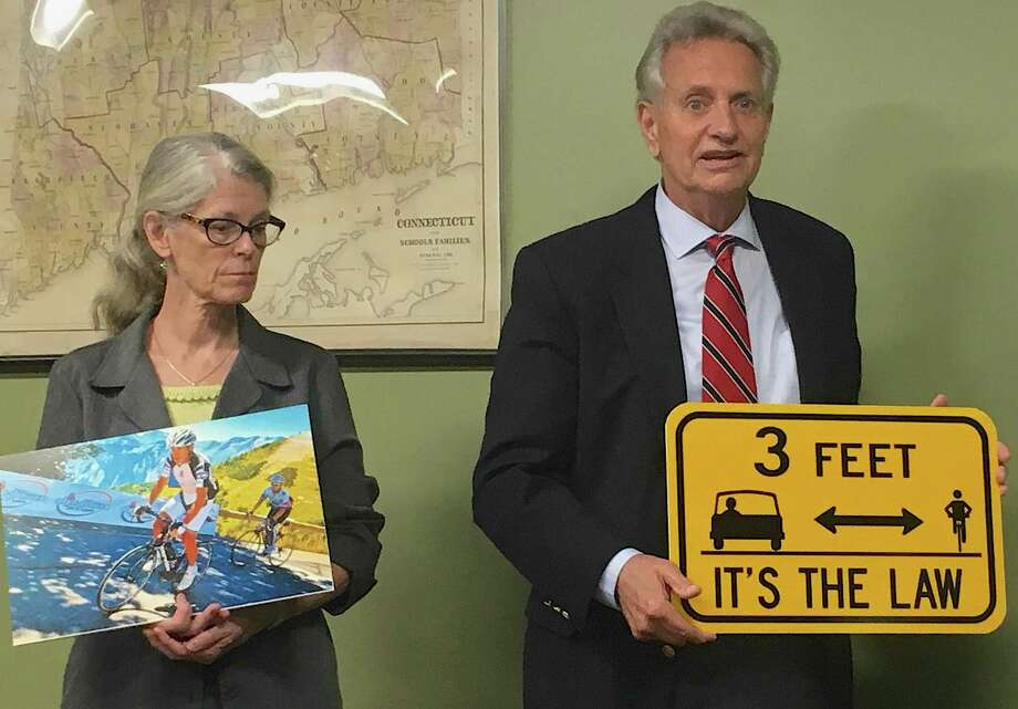 Cramer a& Anderson partners, attorneys Perley Grimes and Dolores Schiesel, present cycling safety signs to the Morris Board of Selectmen in honor of the late attorney David P. Burke. Photo: Photos\ Courtesy Of Cramer & Anderson / Contributed Photo Not For Resale