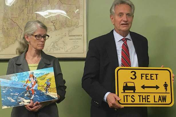 Cramer a& Anderson partners, attorneys Perley Grimes and Dolores Schiesel, present cycling safety signs to the Morris Board of Selectmen in honor of the late attorney David P. Burke.