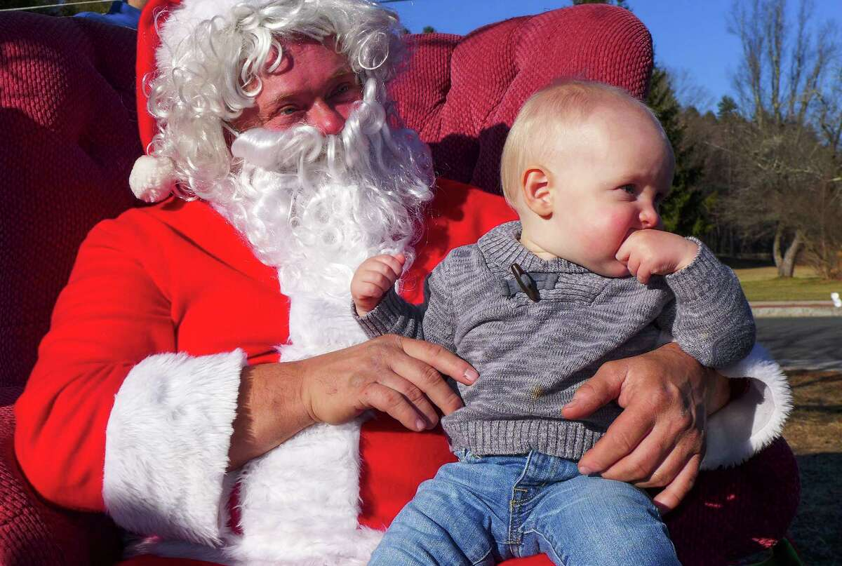 Photo by John Fitts Henry Pfeiffer, 13 months, of Newburyport, Mass ponders what to make of Santa at Christmas in Riverton on Saturday.