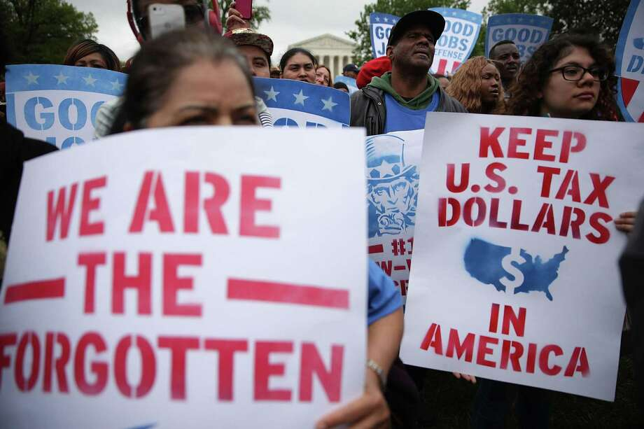 San Antonio and Bexar County recently raised the wages of its lowest paid employees to $14.25 per hours. They are part of a national movement to raise the minimum wage. Here, activists hold signs during a rally in front of the Capitol in April. Photo: Alex Wong /Getty Images / 2017 Getty Images