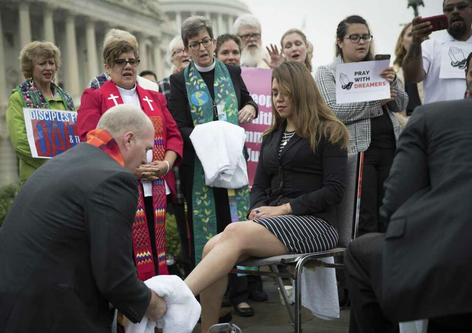 Deyanira Aldana, who was accepted into the Deferred Action for Childhood Arrivals program, has her feet washed by a member of the clergy on Sept. 13 during a demonstration about immigration legislation on Capitol Hill in Washington. The parents of the Dreamers are criminals and DACA recipients have reaped the benefits of their parents' crimes, says a reader. Photo: TOM BRENNER /NYT / NYTNS