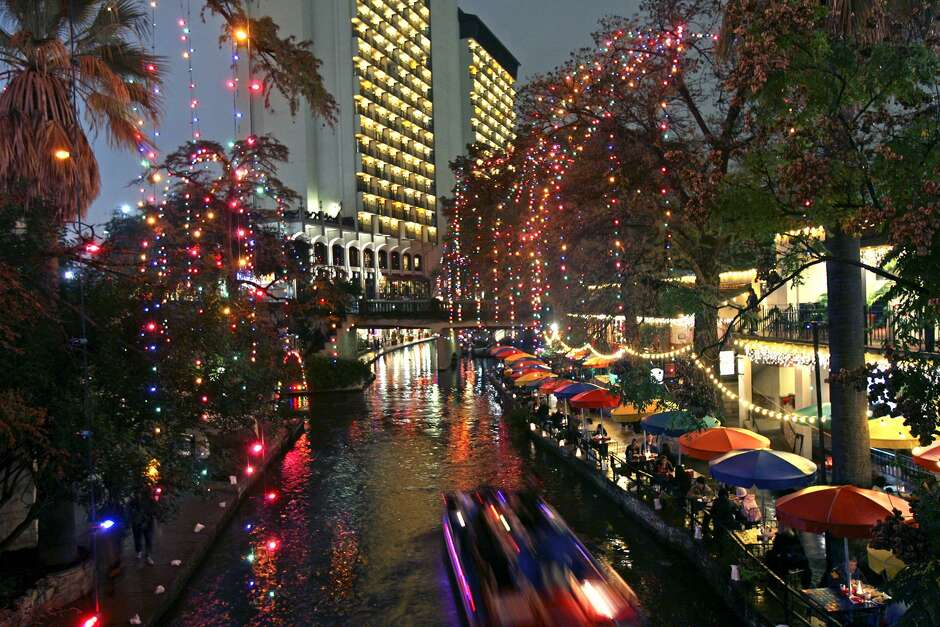barge passengers view the christmas lights on the river walk while riding near the palacio del rio hotel in december 2007