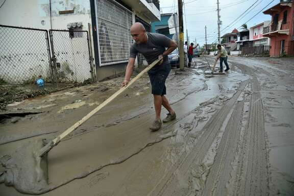 People work cleaning the streets in Toa Baja, Puerto Rico, on Friday after the passage of Hurricane Maria. Rescuers raced against time to reach residents trapped in their homes and the death toll climbed to 33.
