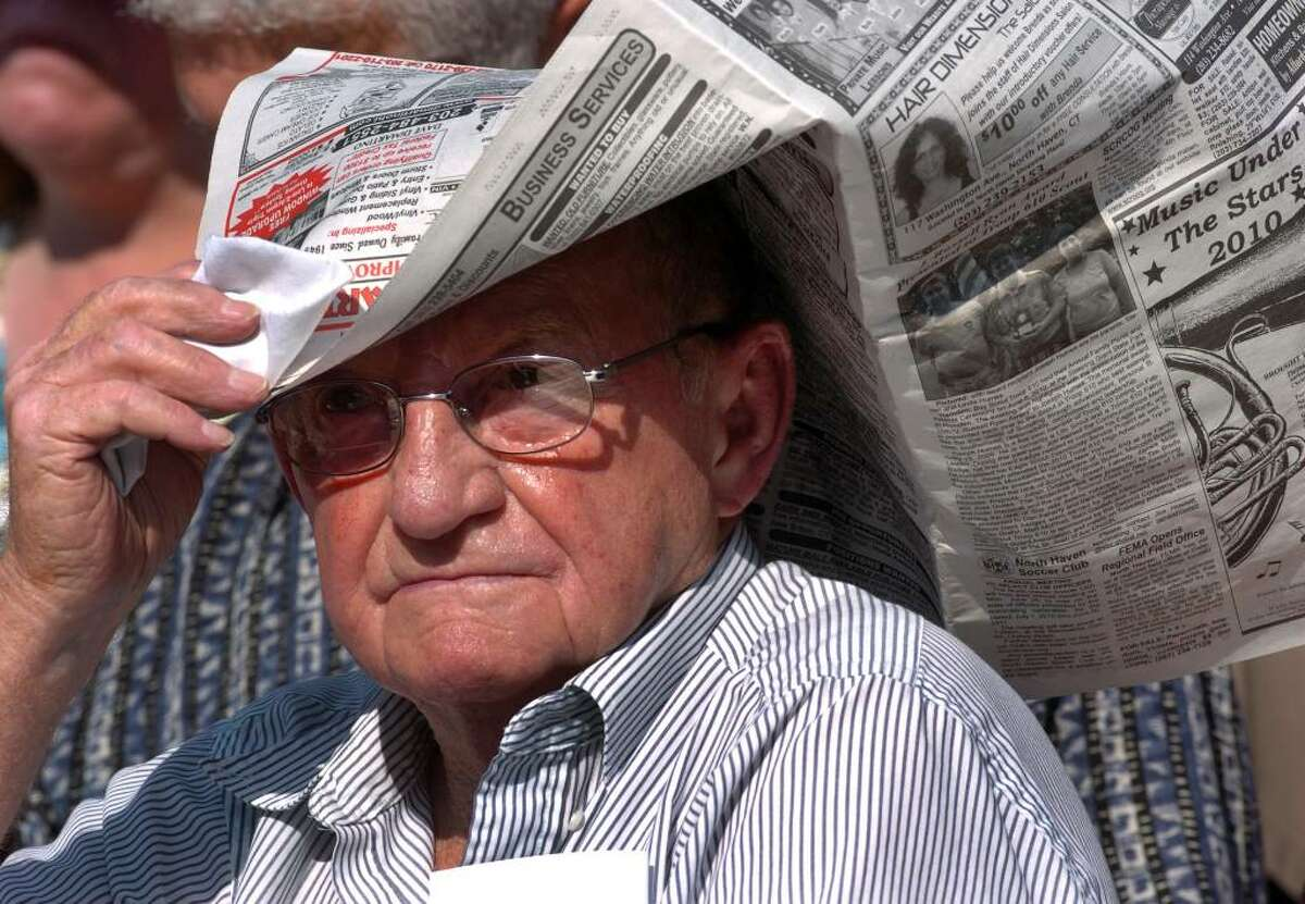 Because of the high temperatures, Millard Haynes, of Wallingford, tries to keep cool by keeping a newspaper on his head, during Foran High School's Graduation Exercises in Milford, Conn. on Wednesday June 23, 2010. Haynes was there to see his granddaughter Arlene Haynes graduate.
