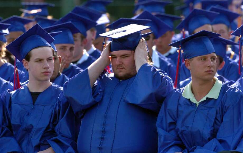 Graduate John Brown, center, adjusts his hat, during Foran High School's Graduation Exercises in Milford, Conn. on Wednesday June 23, 2010. Photo: Christian Abraham / Connecticut Post
