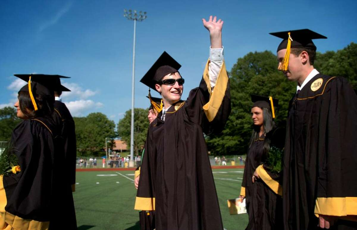 James Vaccaro waves to his family and friends in the audience as he marches onto the football field with his fellow graduates for the 2010 Jonathan Law High School commencement ceremony Wednesday June 23, 2010 at the school in Milford.