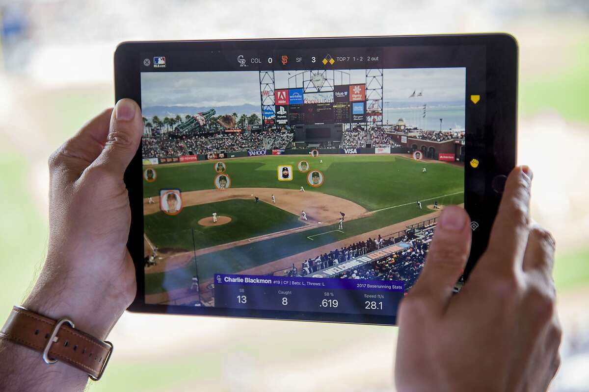 Chad Evans demonstrates the MLB At Batt app as Colorado Rockies Charlie Blackmon (highlighted) runs to second base at the top of the 7th inning at AT&T Park on Wednesday, Sept. 20, 2017, in San Francisco, Calif. Major League Baseball tech executives gave a preview of the new augmented reality portion of the MLB At Bat app, which uses Apple's new ARKit technology. This gives fans at games the ability to use iPhones and iPads to see how big a lead a runner has off first, highlight situations where a steal is likely, see real-time defensive positioning, understand the defensive range of the fielders, and see the gaps where hits would be likely.