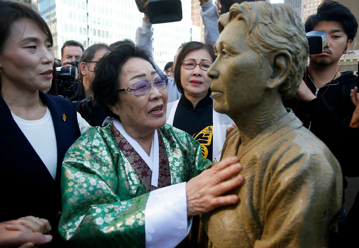 """Former """"comfort woman"""" Grandma Yong-soo Lee reaches out to touch a section of the Comfort Women Memorial statue after it's unveiled at St. Mary's Square park in Chinatown in San Francisco, Calif. on Friday, Sept. 22, 2017. During World War II, thousands of women were captured and used as sex slaves by the Japanese military."""