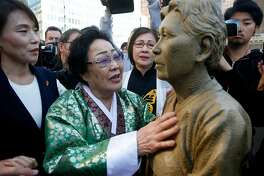 "Former ""comfort woman"" Grandma Yong-soo Lee reaches out to touch a section of the Comfort Women Memorial statue after it's unveiled at St. Mary's Square park in Chinatown in San Francisco, Calif. on Friday, Sept. 22, 2017. During World War II, thousands of women were captured and used as sex slaves by the Japanese military."