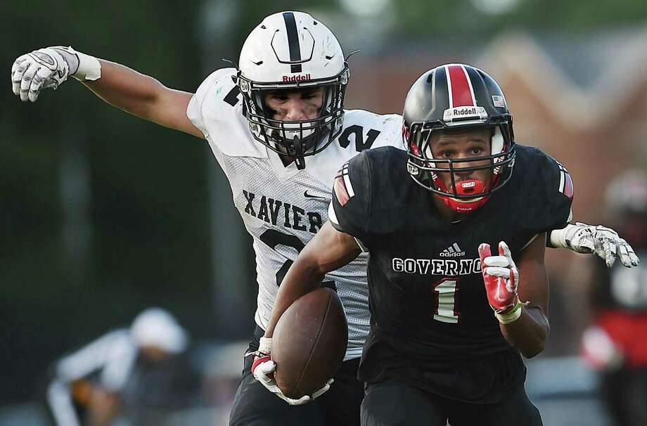 Wilbur Cross' Kwane Taylor advances the ball as Xavier's Nick Hassleman gives chase Friday in New Haven. Wilbur Cross won 14-7. Photo: Catherine Avalone / Hearst Connecticut Media / New Haven Register