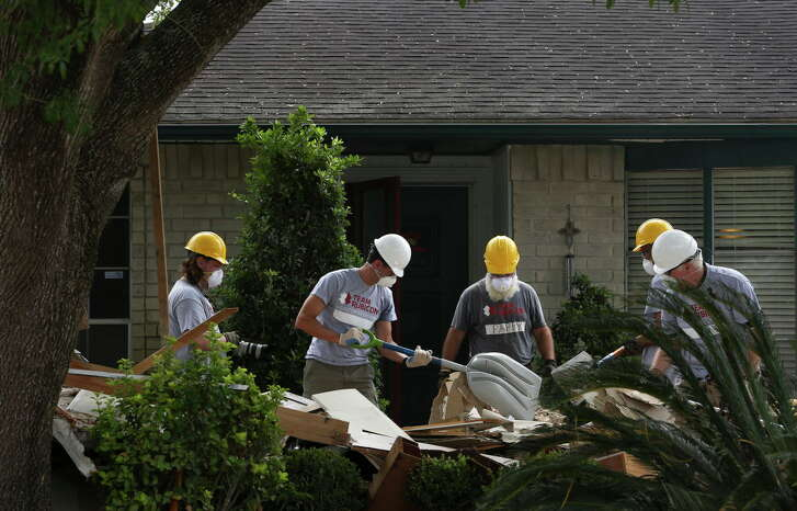 House Speaker Paul Ryan, second left, shovels debris into a wheel barrel while assisrting Team Rubicon Disaster Response to clean out the Harvey-damaged Garcia house on Lucian Lane Thursday, Sept. 21, 2017, in Friendswood.  Ryan was alomg a group of Congressional delegation to help Team Rubicon, a non-profit organization that pairs military veterans with first responders to deploy emergency response teams, with relief efforts in the neighborhood.
