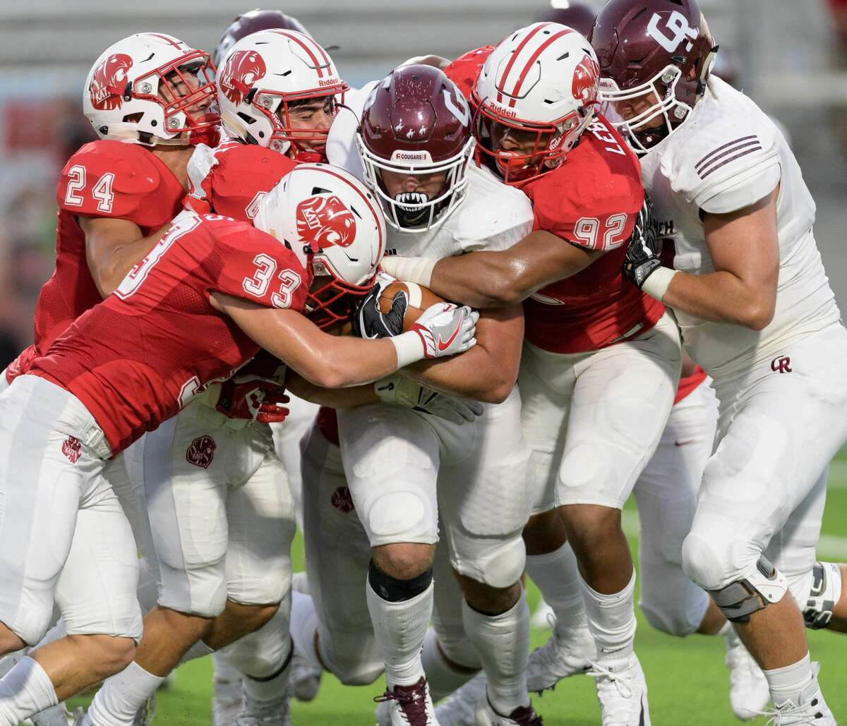 Brant Kuithe (14) of the Cinco Ranch Cougars is brought down for a short gain by Neil Solis (33) and Jonah Lebischal (92) of the Katy Tigers in the first half of a high school football game on Friday, September 22, 2017 at Legacy Stadium in Katy Texas.