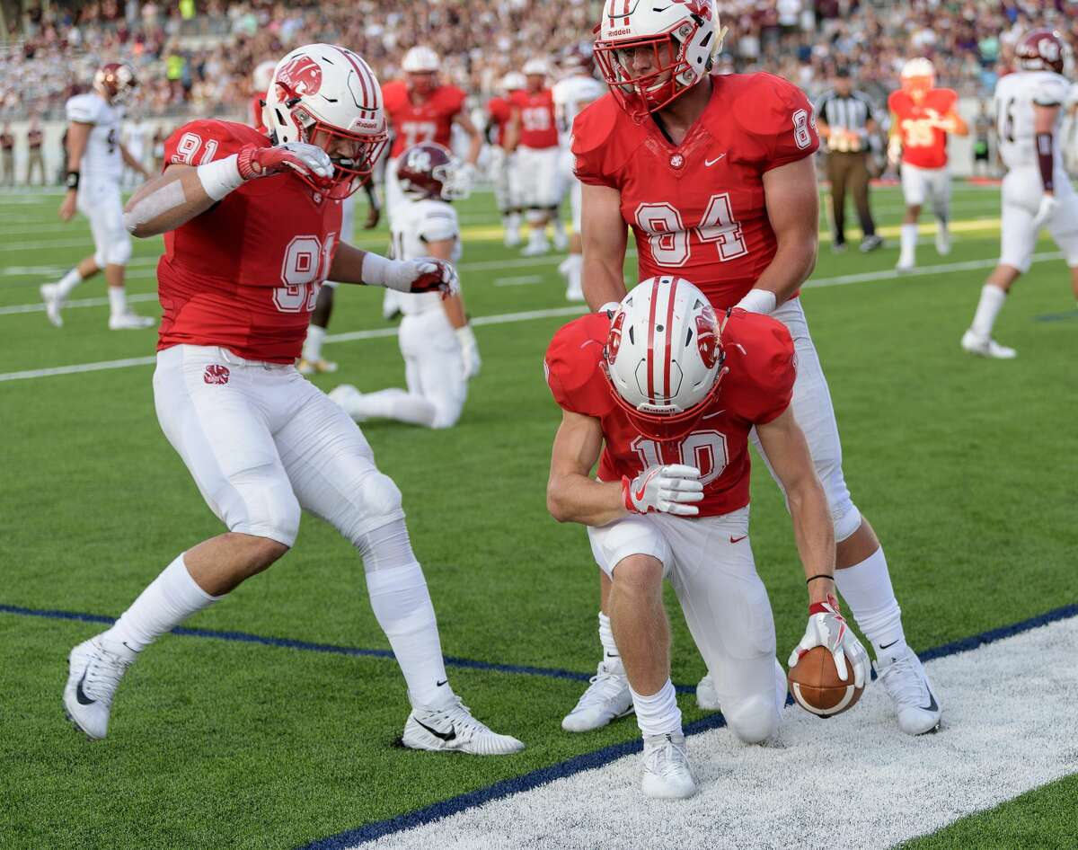 Tyler Pullig (10) of the Katy Tigers celebrates the first touchdown of the game with Michael Matus (91) and Ethan Garner (84) against the Cinco Ranch Cougars in a high school football game on Friday, September 22, 2017 at Legacy Stadium in Katy Texas.