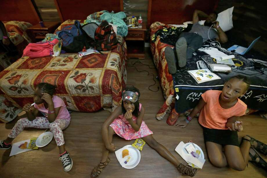 Natalie Spears (from left) and sisters Nevaeh and Makayla watch TV while Brandon Polson talks on the phone Sept. 7 in a Humble-area motel where the flood victims were staying. Photo: Melissa Phillip /Houston Chronicle / © 2017 Houston Chronicle