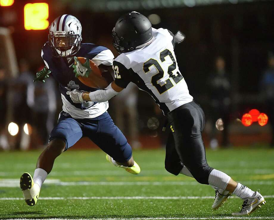 Hillhouse senior wide receiver Terron Mallory avoids a tackle attempt by Amity senior defensive back Matthew Weidenfeller, Friday, Sept. 22, 2017, at the Bowen Field on Crescent Street in New Haven. Hillhouse won, 22-17. Photo: Catherine Avalone, Hearst Connecticut Media / New Haven Register