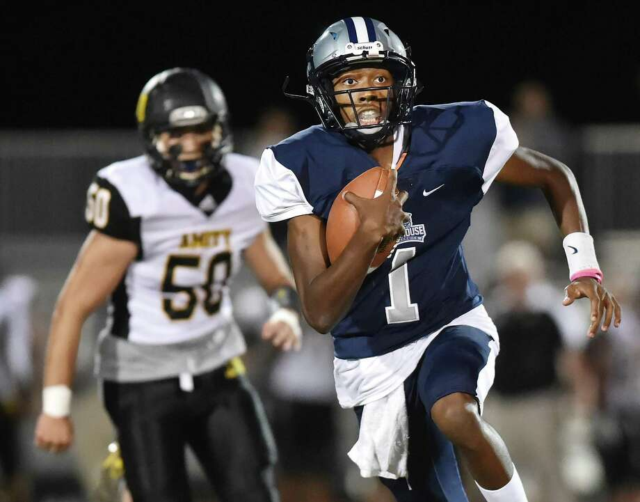 Hillhouse quarterback Dion Watts advances the ball as Amity defensive lineman Daniel Cavanagh gives chase on Friday in New Haven. Photo: Catherine Avalone / Hearst Connecticut Media / New Haven Register