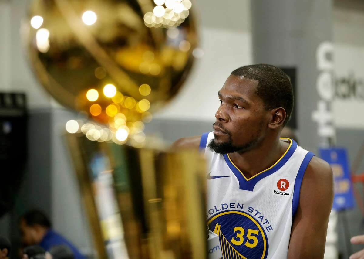 Warriors' Kevin Durant near the Larry O'Brien championship trophy during 2017 media day for the NBA's Golden State Warriors in Oakland, Ca., on Friday September 22, 2017.