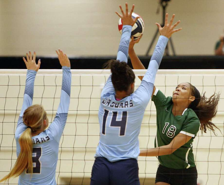 Johnson's Kaylyn Winkler defends against Kyla Waiters of Reagan during a District 26-6A high school volleyball match Sept. 22. Photo: Ron Cortes /For The Express-News