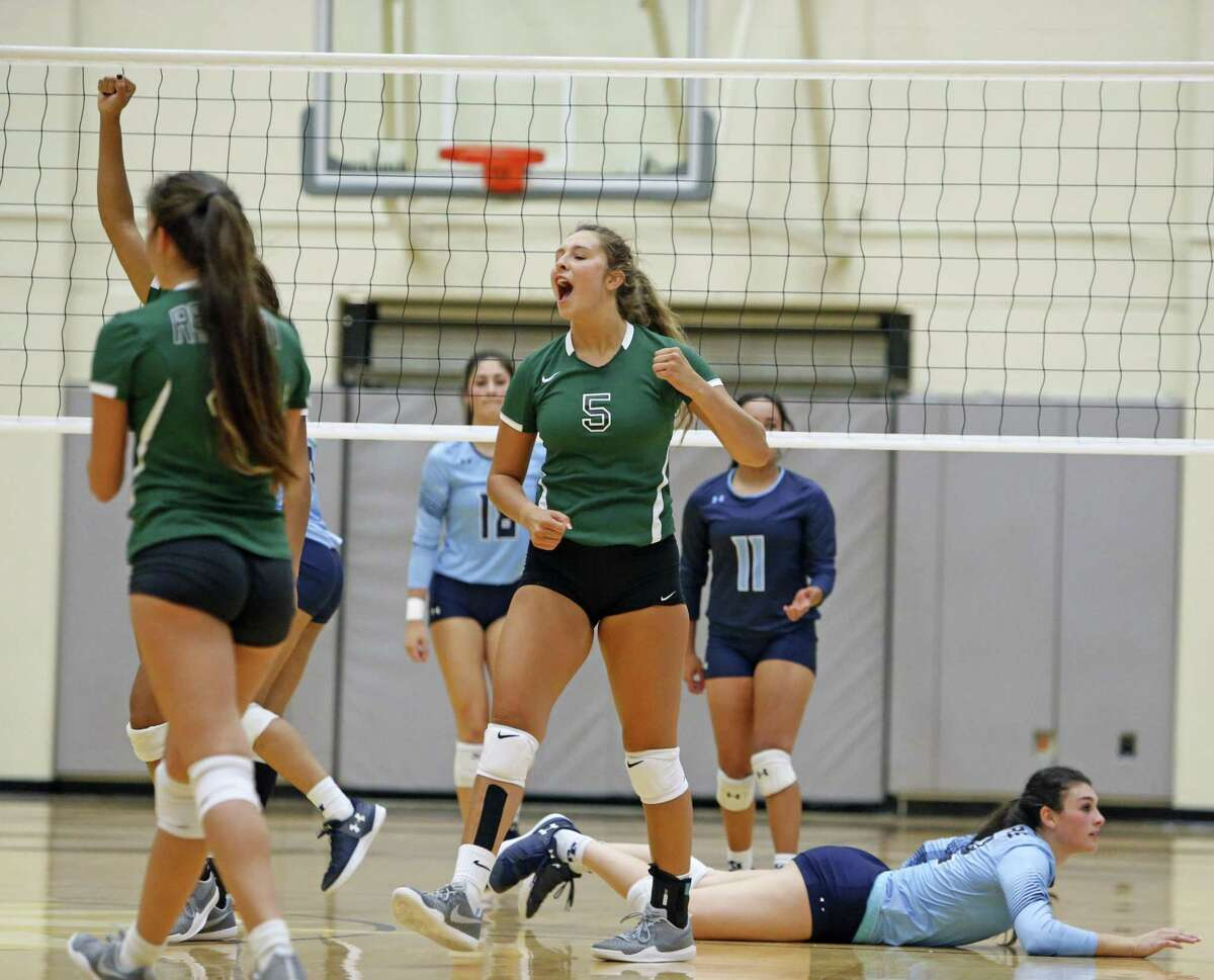 Reagan's Camryn Ennis celebrates with there teammates after a point from the District 26-6A high school volleyball match between Reagan and Johnson on Friday,Sept. 22, 2017