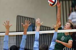 ReaganÕs Camryn Ennis spikes a ball against Johnson from the District 26-6A high school volleyball match between Reagan and Johnson on Friday,Sept. 22, 2017