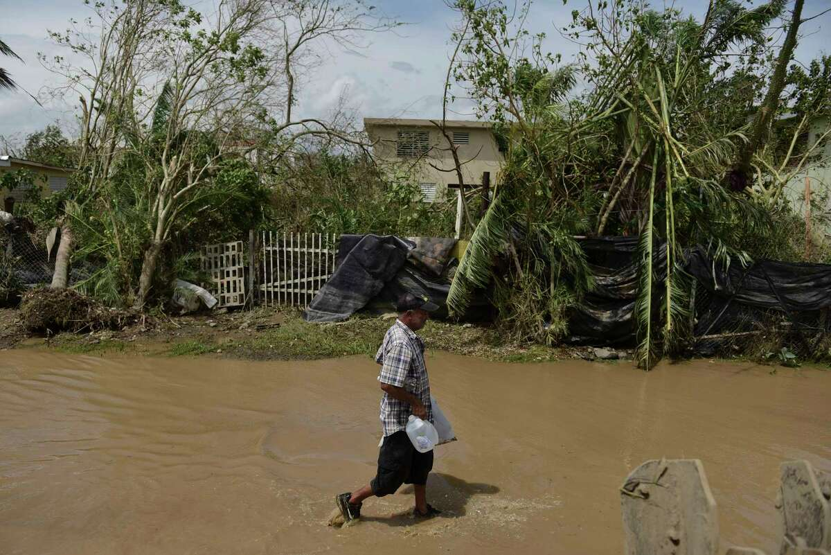 A resident walks on a flooded road after the passing of Hurricane Maria, in Toa Baja, Puerto Rico, Friday, September 22, 2017. Because of the heavy rains brought by Maria, thousands of people were evacuated from Toa Baja after the municipal government opened the gates of the Rio La Plata Dam. (AP Photo/Carlos Giusti) ORG XMIT: CGPR125