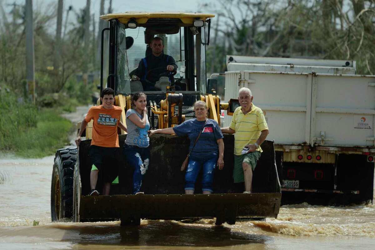 Residents ride a mechanical shovel through a flooded road after the passing of Hurricane Maria, in Toa Baja, Puerto Rico, Friday, September 22, 2017. Because of the heavy rains brought by Maria, thousands of people were evacuated from Toa Baja after the municipal government opened the gates of the Rio La Plata Dam. (AP Photo/Carlos Giusti) ORG XMIT: CGPR109