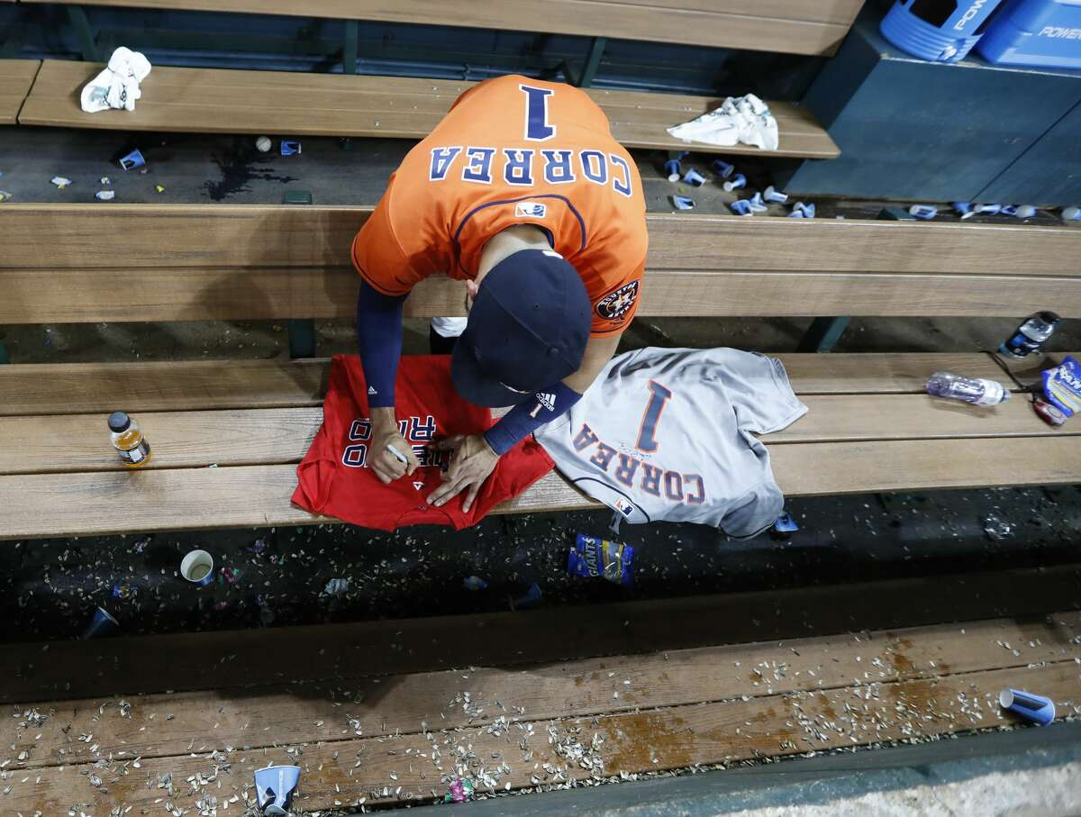 Houston Astros shortstop Carlos Correa (1) signs an autograph on t-shirts in the dugout during the ninth inning of an MLB baseball game at Minute Maid Park, Friday, Sept. 22, 2017, in Houston. ( Karen Warren / Houston Chronicle )
