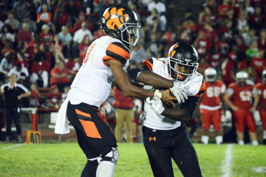 Edwardsville quarterback Kendall Abdur-Rahman, left, hands the ball off to Antonio Thigpen Jr. in the first half of Friday's Southwestern Conference game at Alton.